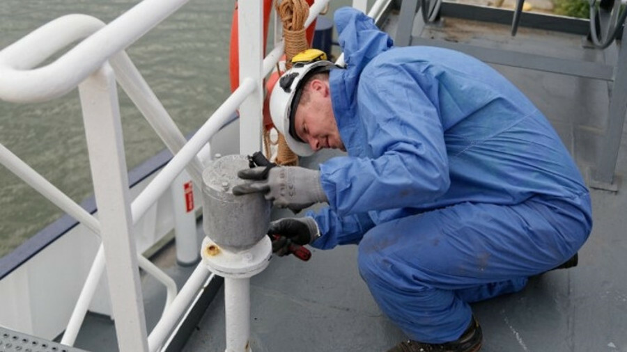 An inspector collects samples from the ship to be analysed in accredited laboratories