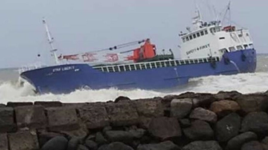 A general cargo ship remains grounded on a rocky coastline while discussions continue