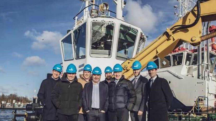 Management teams from Damen and S Walsh & Sons stand in front of a multicat workboat that will be ad