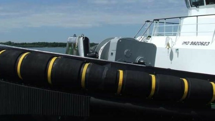 Cylindrical fenders on the bow of a harbour tug absorb energy during berthing operations