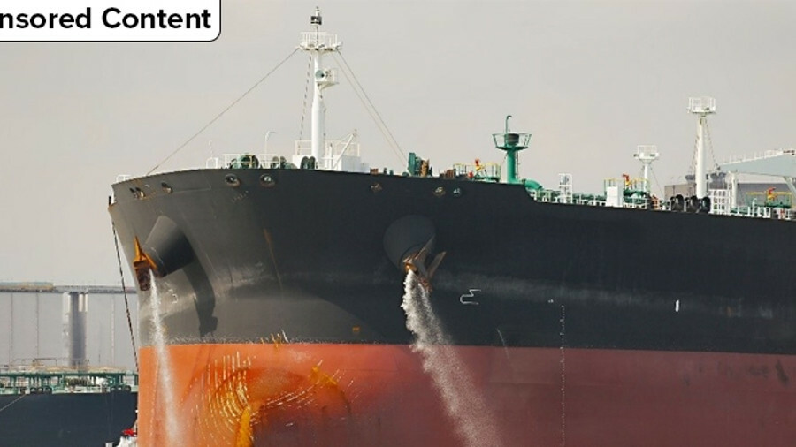 Large tanker pumping out ballast water when coming into port
