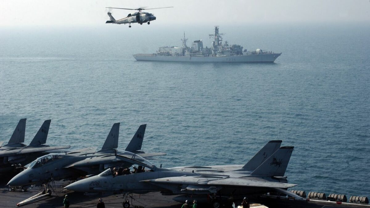 HMS Montrose is dwarfed by the US aircraft carrier USS Theodore Roosevelt