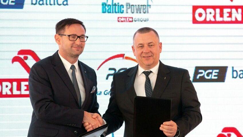 PKN Orlen's Daniel Obajtek and PGE's Henryk Baranowski shake hands