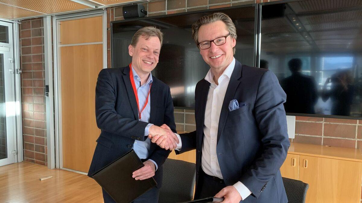 (l-r) Roger Holm (Wärtsilä) shakes hands with Knut Ørbeck-Nilssen (DNV GL)