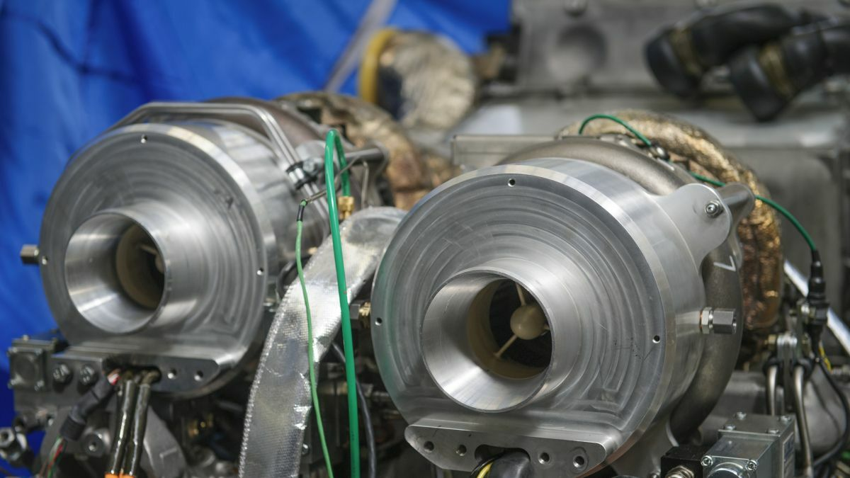 Two 'cook pot-type' aluminium covers fitted in front of the turbocharger compressor on a 10-cylinder diesel engine conceal new electrically assisted turbocharging technology